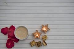浪漫冬天摄影图象用热的泡沫的牛奶饮料和豪华巧克力和红色玫瑰花瓣和星形状点燃了蜡烛 免版税库存照片