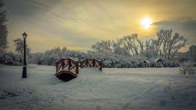 浪漫冬天横向 用在多云天气的雪盖的一个美丽如画的晚上城市公园 有一个的木桥的一条小径 免版税库存图片
