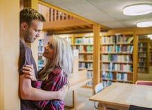 年轻浪漫加上书架在距离在图书馆里 免版税库存照片