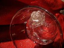 浪漫华伦泰玻璃在绝对红色背景的清楚的水中上升了 库存照片