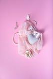 浪漫卡片或邀请 心脏,壳,面纱,在桃红色背景的丝绸丝带 顶视图 免版税库存图片