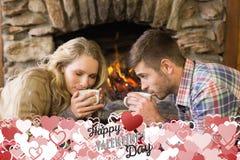 浪漫在被点燃的壁炉前面的夫妇饮用的茶的综合图象 免版税库存图片