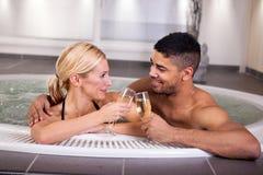 浪漫在浴盆的夫妇饮用的cahmpagne 库存照片