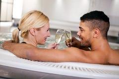 浪漫在浴盆的夫妇饮用的cahmpagne 库存图片