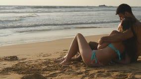 年轻浪漫夫妇享受美丽的景色坐海滩和拥抱 妇女和一个人一起坐  免版税库存照片