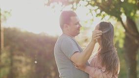 浪漫夫妇在一个绿色夏天公园 她的男朋友的胳膊的一个女孩 愉快一起,打旋在光芒  股票视频