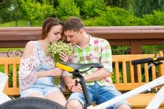 浪漫夫妇坐一朵长凳和嗅到的花在同水准 库存图片