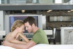 浪漫夫妇坐沙发在客厅 免版税库存照片