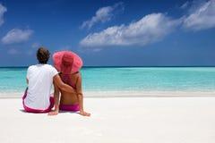 浪漫夫妇拥抱坐一个热带海滩 库存图片