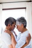 浪漫夫妇拥抱面对面在卧室 免版税库存照片