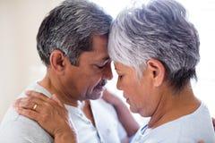 浪漫夫妇拥抱面对面在卧室 免版税库存图片