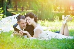 浪漫夫妇放松室外在湖在夏天绿色公园在开花晚上阳光下与火光 库存照片