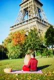 浪漫夫妇有在草的野餐在埃菲尔铁塔附近 免版税库存图片