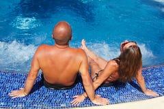 浪漫夫妇松弛近的水池 免版税库存照片