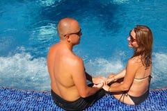 浪漫夫妇松弛近的水池 免版税图库摄影