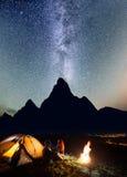 浪漫夫妇游人坐面对面在前面帐篷在篝火附近下在晚上发光满天星斗的天空 免版税库存照片