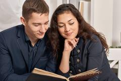浪漫夫妇饮用的茶用曲奇饼,谈和看相册 图库摄影