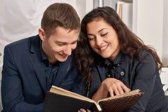 浪漫夫妇饮用的茶用曲奇饼,谈和看相册 库存照片