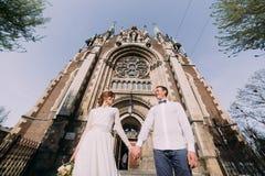 浪漫夫妇,摆在举行的新婚佳偶valentynes在老哥特式教会附近递 库存照片