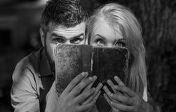 浪漫夫妇 在爱的夫妇读了古老书,黑暗的背景 库存图片
