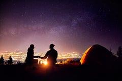 浪漫夫妇临近营火在满天星斗的天空 免版税图库摄影