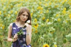 浪漫妇女与起来了说谎在向日葵领域 库存照片