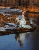 浪漫妇女画象一件礼服的在河的河岸 免版税库存图片