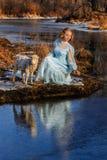 浪漫妇女画象一件礼服的在河的河岸 库存图片