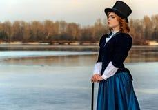 浪漫妇女画象葡萄酒礼服的在河 库存照片