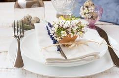浪漫婚礼或复活节桌设置,淡紫色,白色板材,在蛋壳的花 图库摄影