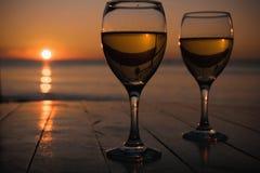 浪漫室外活动 两块玻璃用白葡萄酒在一家室外餐馆有日落海视图,两的放松概念 免版税库存图片