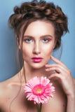 浪漫少妇画象有看在蓝色背景的桃红色花的照相机 春天时尚照片 spri的启发 免版税库存照片