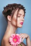 浪漫少妇画象有看在蓝色背景的桃红色花的照相机 春天时尚照片 spri的启发 图库摄影