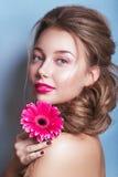 浪漫少妇画象有看在蓝色背景的桃红色花的照相机 春天时尚照片 spri的启发 库存图片