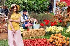 浪漫帽子的逗人喜爱的少妇走在乔治亚节日的收获庭院的  免版税库存图片
