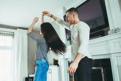 浪漫年轻人微笑的笑的夫妇供以人员拥抱的爱的,亲吻妇女,一起跳舞 免版税库存图片