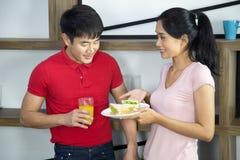 浪漫年轻可爱的夫妇展示三明治在厨房里 库存照片