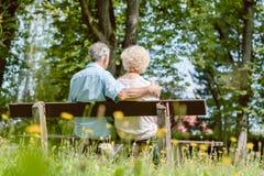 浪漫年长夫妇一起坐在tranqui的一条长凳 免版税库存照片