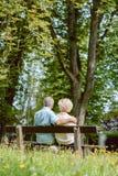 浪漫年长夫妇一起坐在tranqui的一条长凳 免版税库存图片