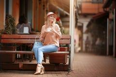 浪漫心情的可爱的妇女微笑在幸福的坐对穿桃红色夹克的桌 免版税库存照片