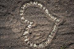 以浪漫心脏的形式白花在沙子 免版税库存照片