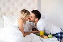 浪漫愉快的夫妇吃早餐在床 免版税库存照片
