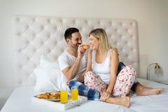 浪漫愉快的夫妇吃早餐在床 库存照片