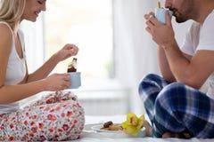 浪漫愉快的夫妇吃早餐在床 免版税库存图片