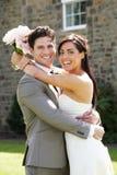 浪漫拥抱的新娘和新郎户外 免版税库存图片