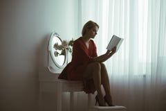 浪漫故事 端庄的妇女读了浪漫故事 与浪漫故事的书 浪漫故事读书 想象力 免版税库存图片