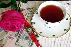 浪漫早晨 浪漫行程 浪漫早晨 在桌上是葡萄酒手表,上升了,金钱,站立在一杯茶旁边 库存图片