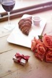 浪漫早餐为华伦泰` s天庆祝概念 新鲜的面包店新月形面包,红葡萄酒,在木桌上的玫瑰色花 库存图片