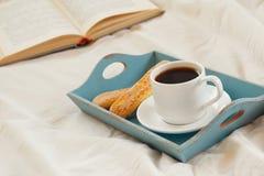 浪漫早餐在床上:曲奇饼、热的咖啡和开放书 免版税库存照片