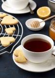 浪漫早餐在情人节用心形的曲奇饼和茶在石背景的 图库摄影